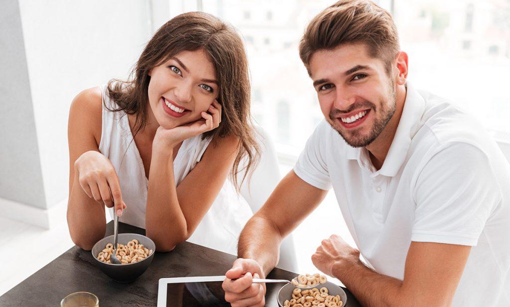 Pár s tabletami s prázdnou obrazovkou s raňajkami v kuchyni