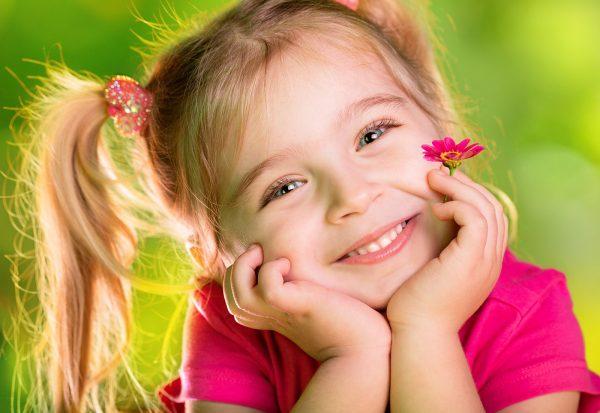 Μικρό κορίτσι σκέφτεται με τη μαργαρίτα την άνοιξη πράσινο